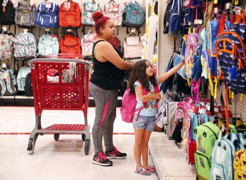 Kristie Díaz, residente de Dallas ayuda a su hija Aubrie, 5, a recoger una mochila en Target. El fin de semana libre de impuestos, o tax-free weekend arranca el viernes. (Por TOM FOX/DMN)