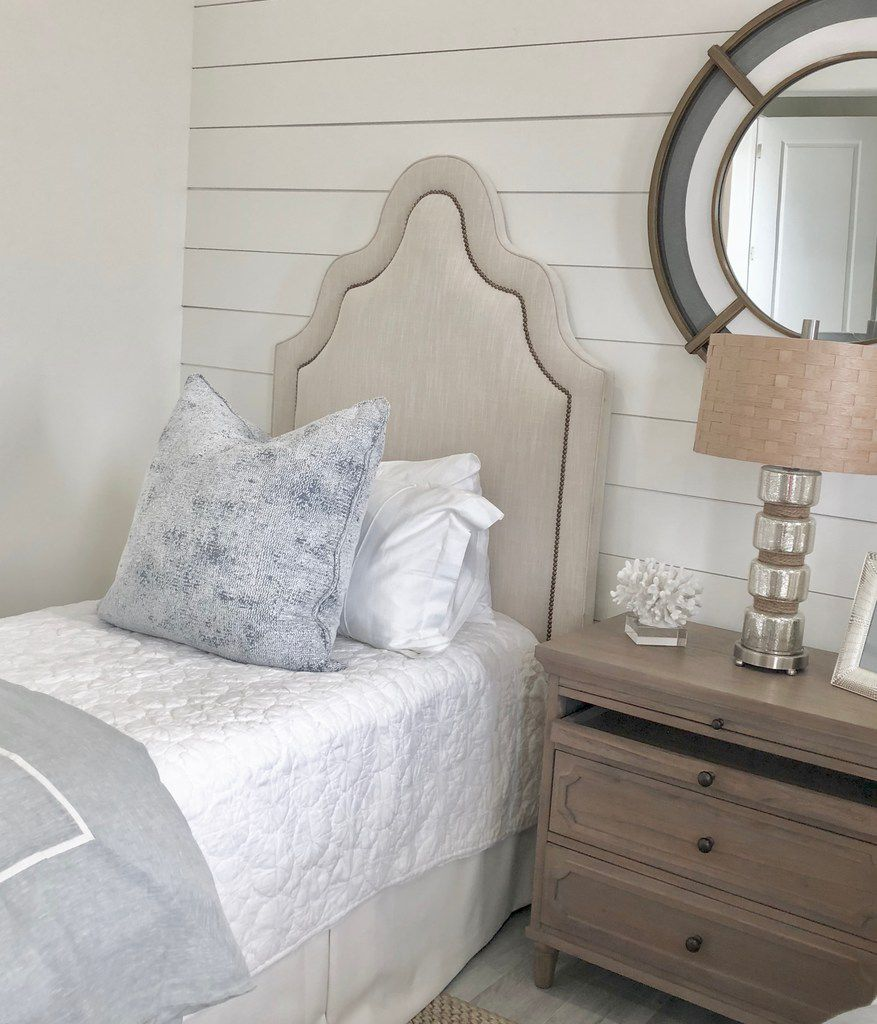 Natural fabrics and fibers create a tranquil and casual feel in this beach house guest room designed by Emily Sheehan Hewett and A Well Dressed Home.