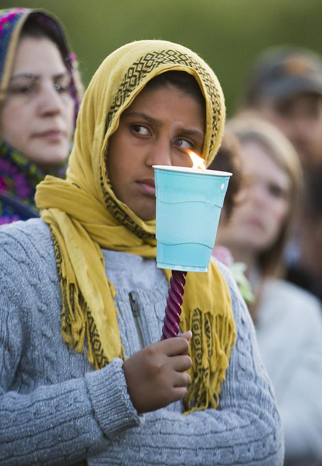 """Fajor Ahmed of Sachse holds a candle during the """"Remember His Name: Vigil for Jordan Edwards"""" candlelight vigil at Virgil T. Irwin Park on Thursday, May 4, 2017, in Balch Springs, Texas."""