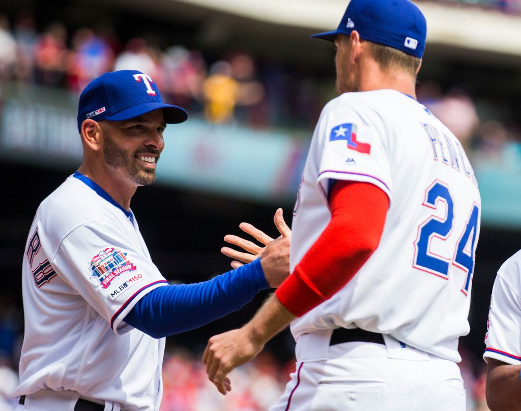 Texas Rangers manager Chris Woodward (8) greets designated hitter Hunter Pence (24) before an opening day MLB game between the Texas Rangers and the Chicago Cubs on Thursday, March 28, 2019 at Globe Life Park in Arlington, Texas. (Ashley Landis/The Dallas Morning News)