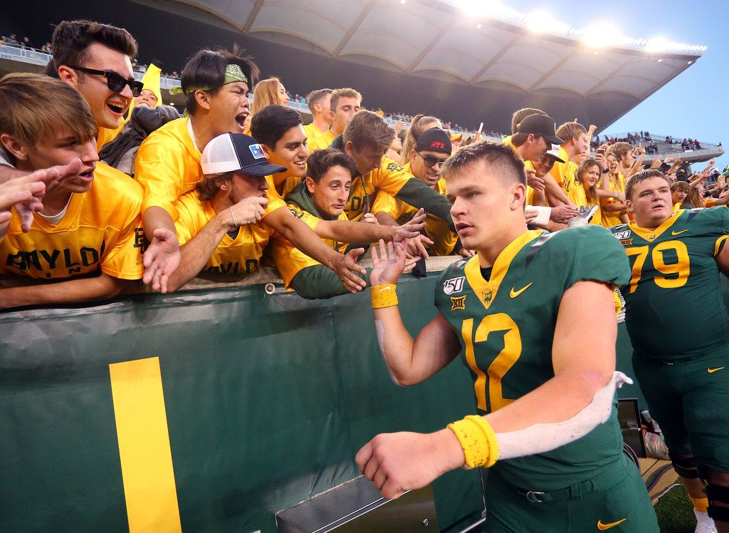WACO, TEXAS - OCTOBER 12:  Quarterback Charlie Brewer #12 of the Baylor Bears high fives fans after the overtime win against the Texas Tech Red Raiderson October 12, 2019 in Waco, Texas. (Photo by Richard Rodriguez/Getty Images)
