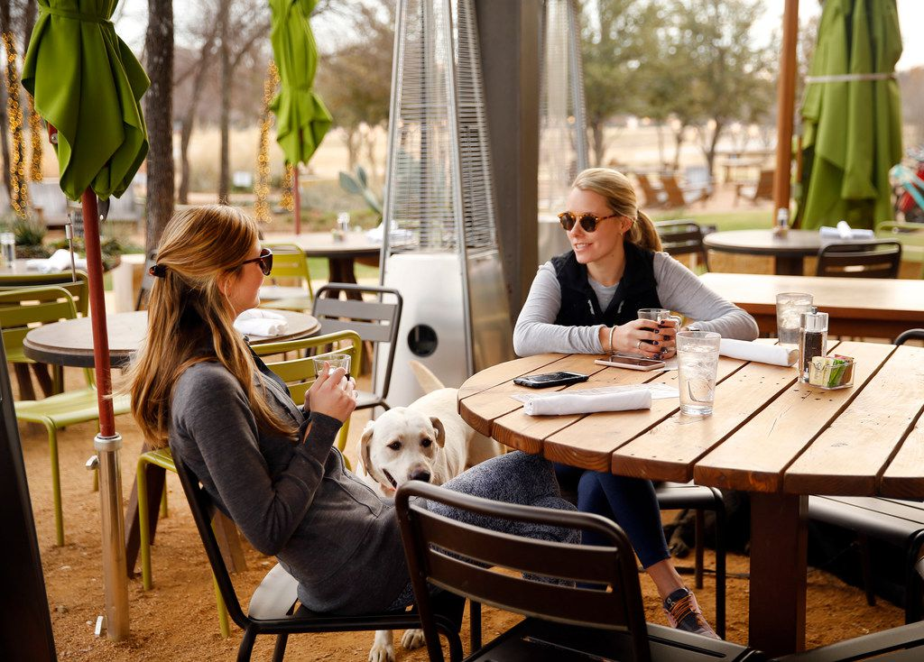 Mary Clay Carr (left) and Emma Grace Laird, both of Auburn, Alabama keep warm on the patio of the Press Cafe with a cup of coffee.