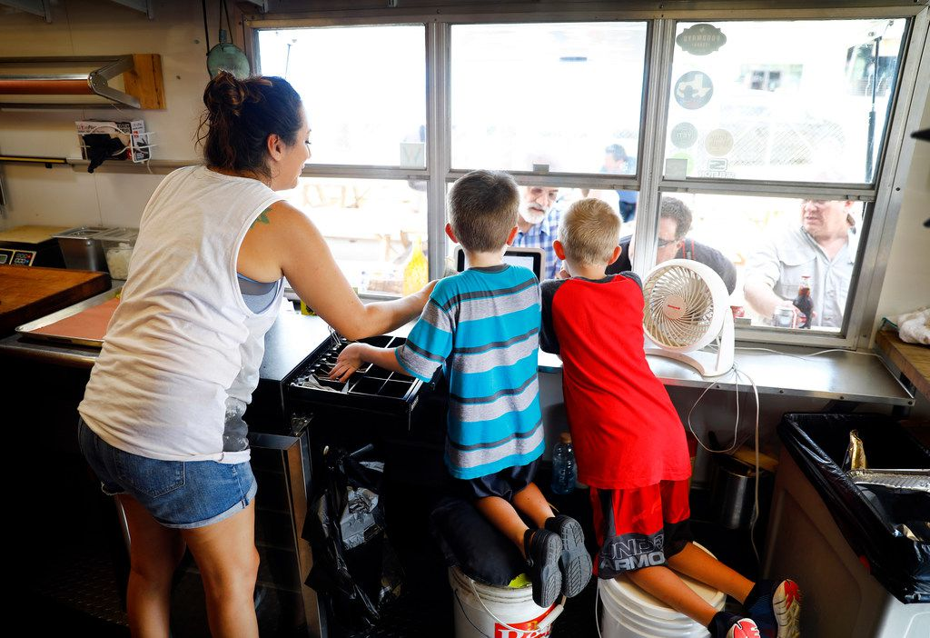 Brandi Alejandro (left) helps Elliot Guess (center) and Ryan Hayes take orders at the trailer window of Guess Family Barbecue in Waco. Guess, 7, is the son of the owners.