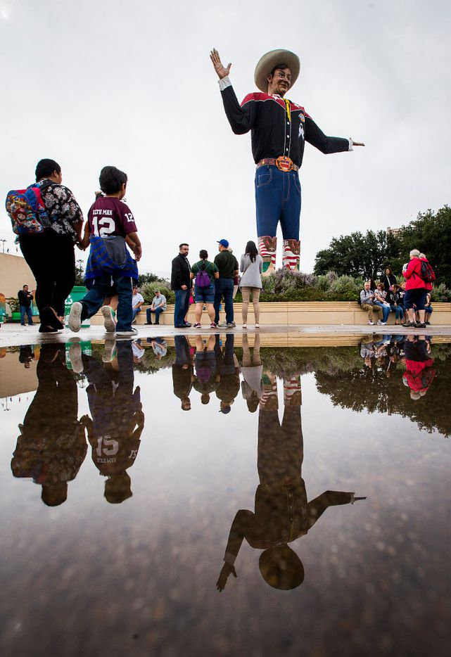 Big Tex is reflected as fairgoers avoid a puddle left by a morning rain during the State Fair of Texas at Fair Park on Friday, Oct. 14, 2016, in Dallas. (Smiley N. Pool/The Dallas Morning News)