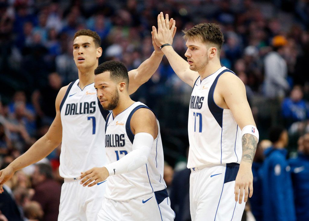 Dallas Mavericks forward Luka Doncic (77) slaps hands with forward Dwight Powell (7) as they and guard Jalen Brunson (13) walk to the bench during a fourth quarter timeout at the American Airlines Center in Dallas, Wednesday, April 3, 2019. (Tom Fox/The Dallas Morning News)