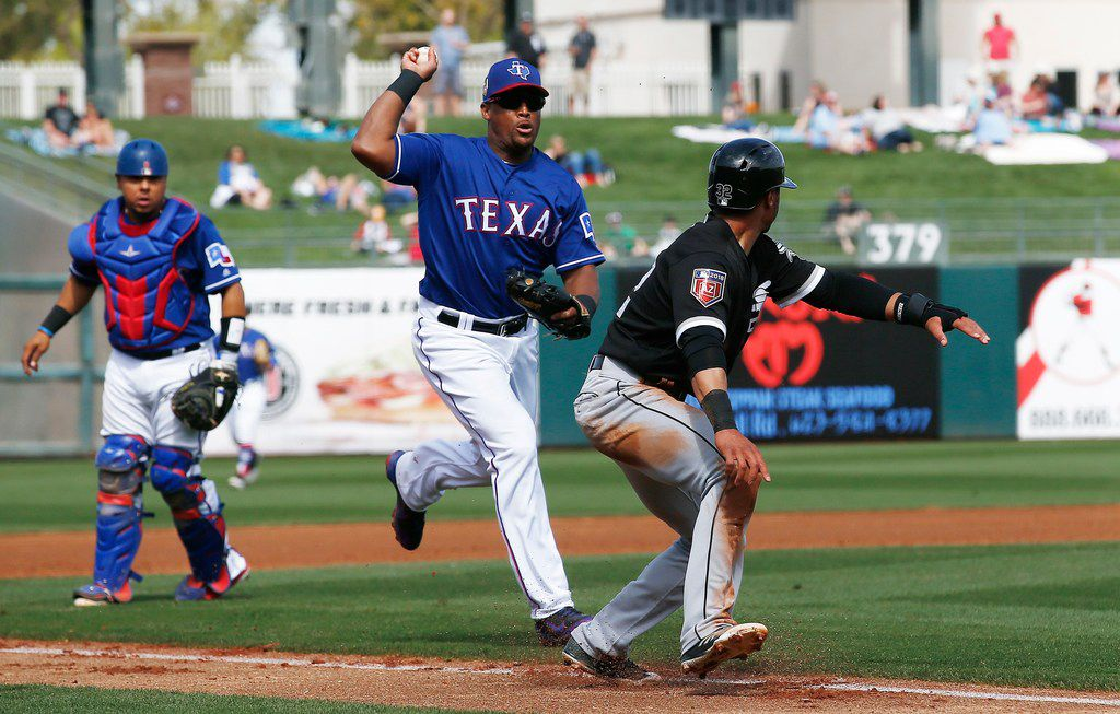 Texas Rangers third baseman Adrian Beltre, center, chases Chicago White Sox's Jacob May, right, in a rundown before tagging May out as Rangers catcher Juan Centeno, left, looks on during the third inning of a spring training baseball game Thursday, March 8, 2018, in Surprise, Ariz. (AP Photo/Ross D. Franklin)