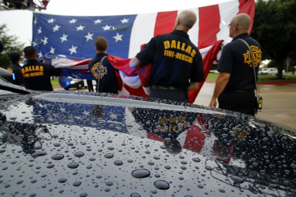 Under a light rain fall, Plano and Dallas fire departments prepare to fly a large U.S. flag above the main entrance to Prestonwood Baptist Church in Plano, Texas for the service and memorial of Dallas police officer Michael Krol, Friday, July 15, 2016. Krol was gunned down in an ambush attack in downtown Dallas a week ago. Four Dallas police officers and one DART officer were killed and several survived. (Tom Fox/The Dallas Morning News)