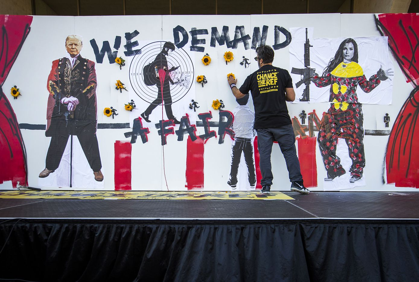 """Manuel Oliver places flowers in holes to symbolize the victims of a mass shooting at Marjory Stoneman Douglas High School in Parkland, Florida, as he creates a """"Wall of Demand"""" during a gun control demonstration outside Dallas City Hall organized by StudentsMarch.org during the NRA Annual Meeting & Exhibits at the Kay Bailey Hutchison Convention Center on Saturday, May 5, 2018, in Dallas. Oliver's son Joaquin was one of the 17 victims of the shooting."""