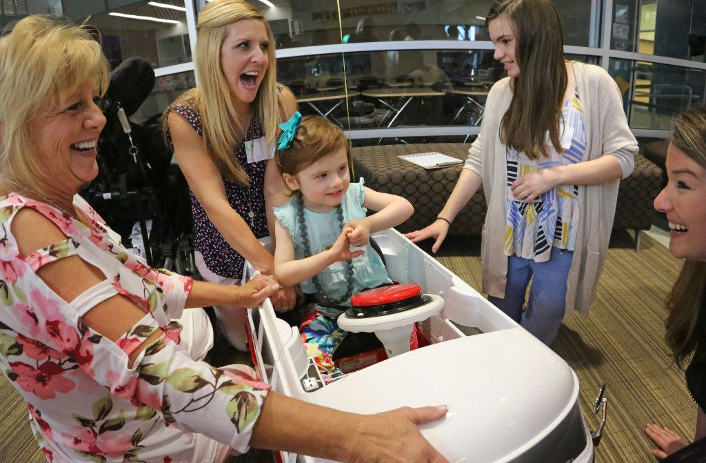Frisco teacher Janna Medcalf, therapist Aubrey Selbo, Liberty High School student Molly Lammes and Meggan Jackson, left to right, get ready to assist three-year-old Abbi Jackson, as special needs children enjoy driving motorized toy cars retrofitted by Frisco schools engineering students at the Frisco ISD Career and Technical Education Center on Wednesday, May 24, 2017. Lammes worked to modify the car to fit Abbi's special needs. (Louis DeLuca/The Dallas Morning News)