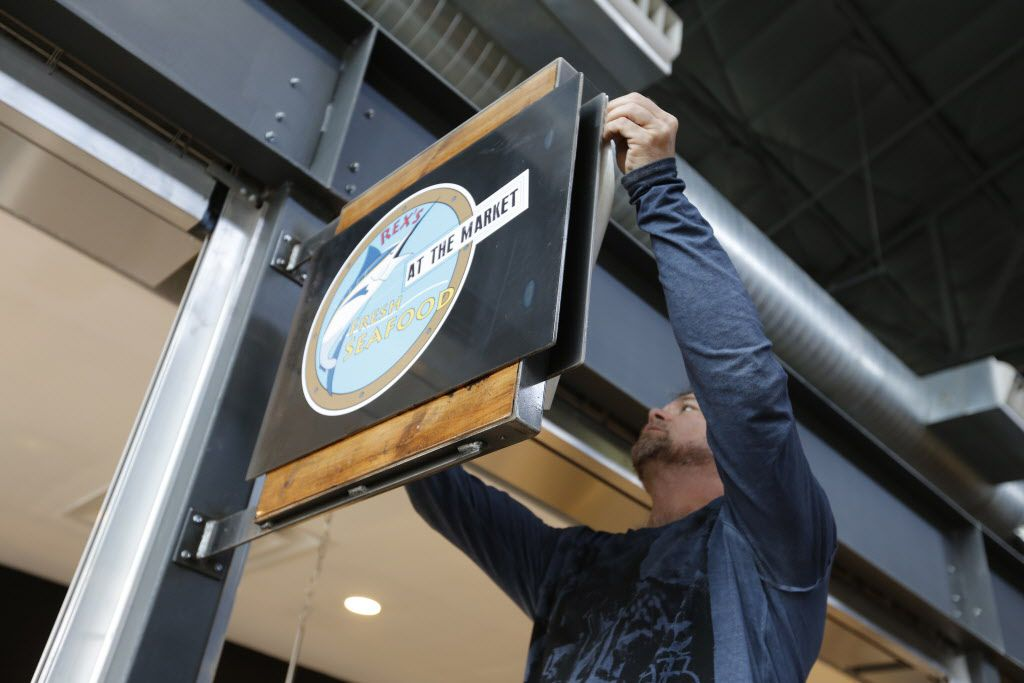 Todd Wingo with Gigantic Color places a Rex's Fresh Seaford sign at The Market's soft opening at the Dallas Farmers Market Friday December 11, 2015.  (Ron Baselice/The Dallas Morning News)   [ This is located in the building formerly called Shed 2 at the Dallas Farmers Market ]