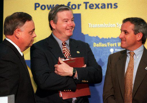 In this file photo, Rep. Joe Barton speaks with Mike Greene, president of TXU Electric, and Brett Perlman of the Public Utility Commission after a news conference in Dallas. (Photo by Jon Freilich)