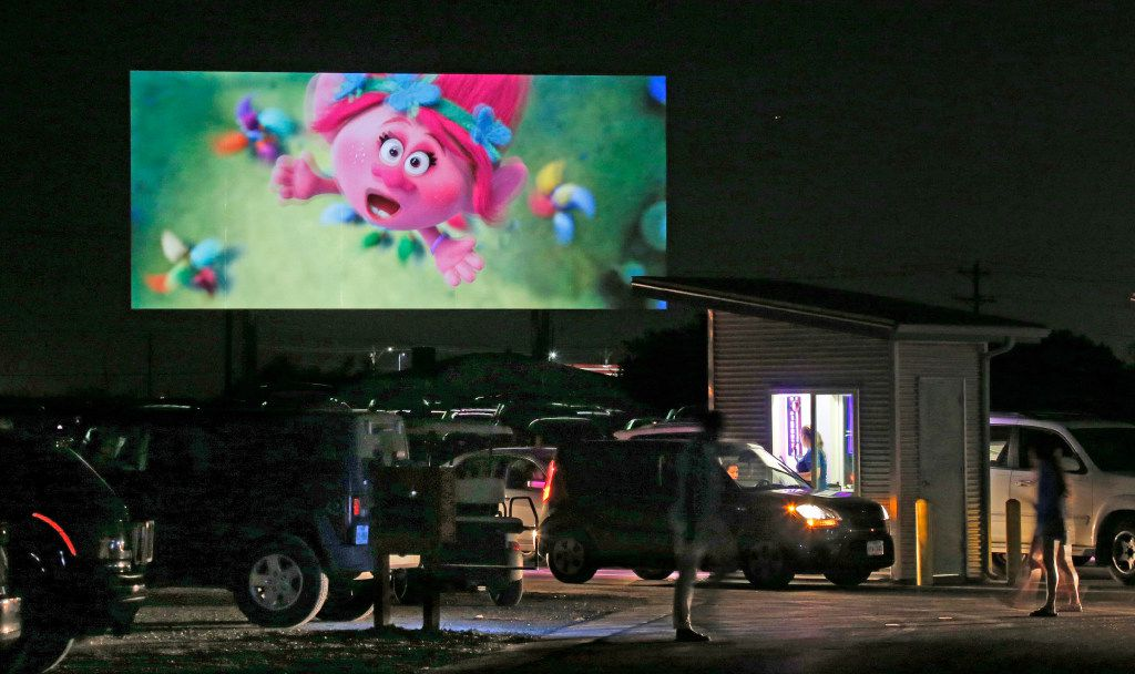 """Movie fans continue to arrive as a screen shows the """"Coming Attractions"""" reel at the Coyote Drive-In in Lewisville, Texas, photographed on Saturday, October 29, 2016. (Louis DeLuca/The Dallas Morning News)"""