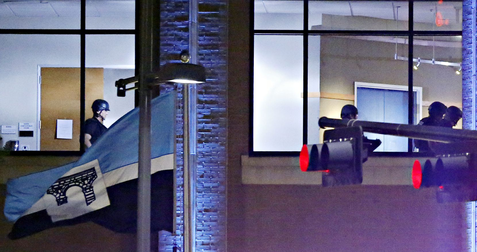 Dallas Police SWAT team members walk in a second story floor at El Centro College, early in the morning of July 8, close to the time that an explosion was heard in the building following a deadly shooting Friday, July 7, 2016 in Dallas.