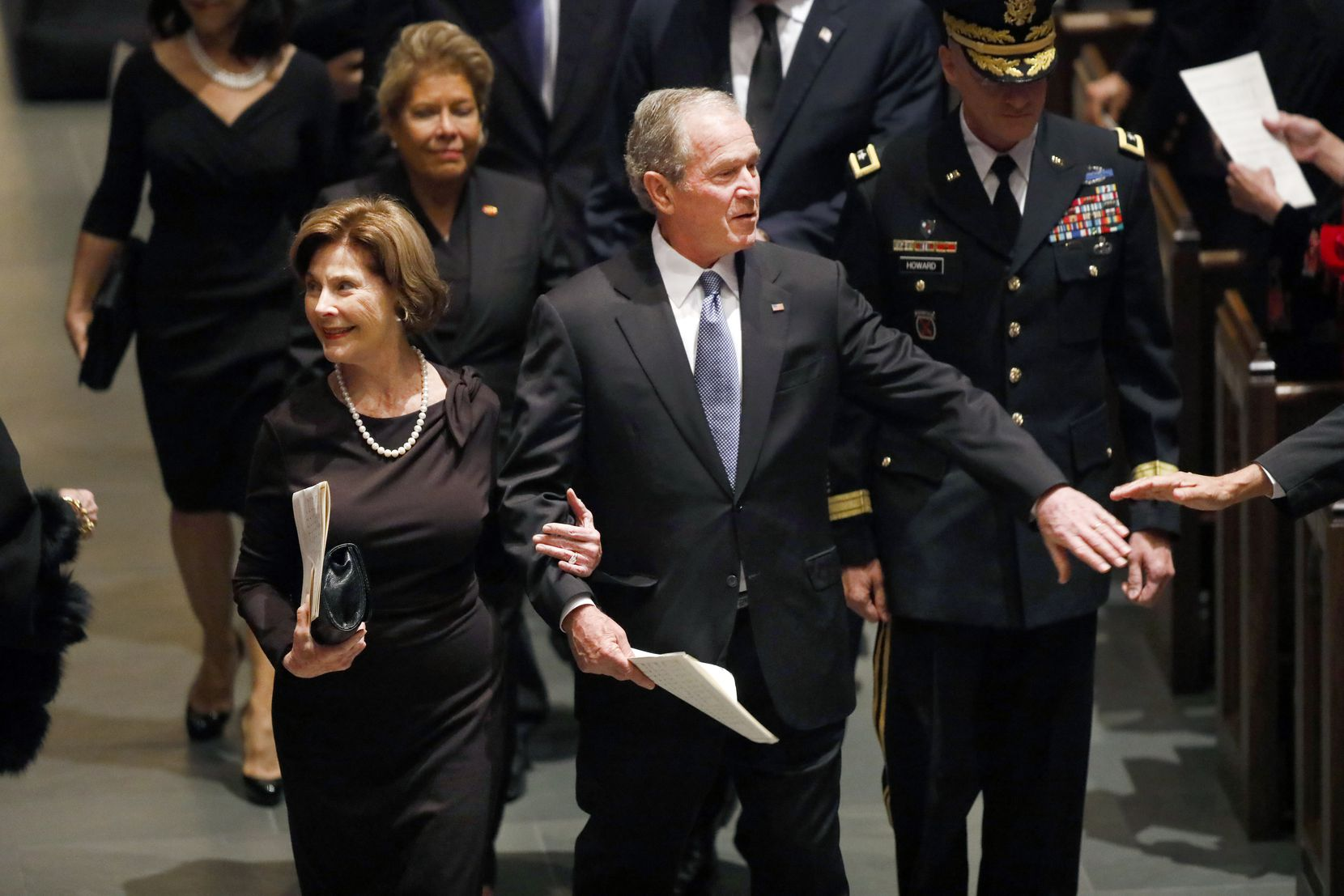 Former President George W. Bush and First Lady Laura Bush are greeted by well-wishers during the funeral recessional for George H.W. Bush, the 41st President of the United States, at St. Martin's Episcopal Church in Houston, Thursday, December 6, 2018. (Tom Fox/The Dallas Morning News)