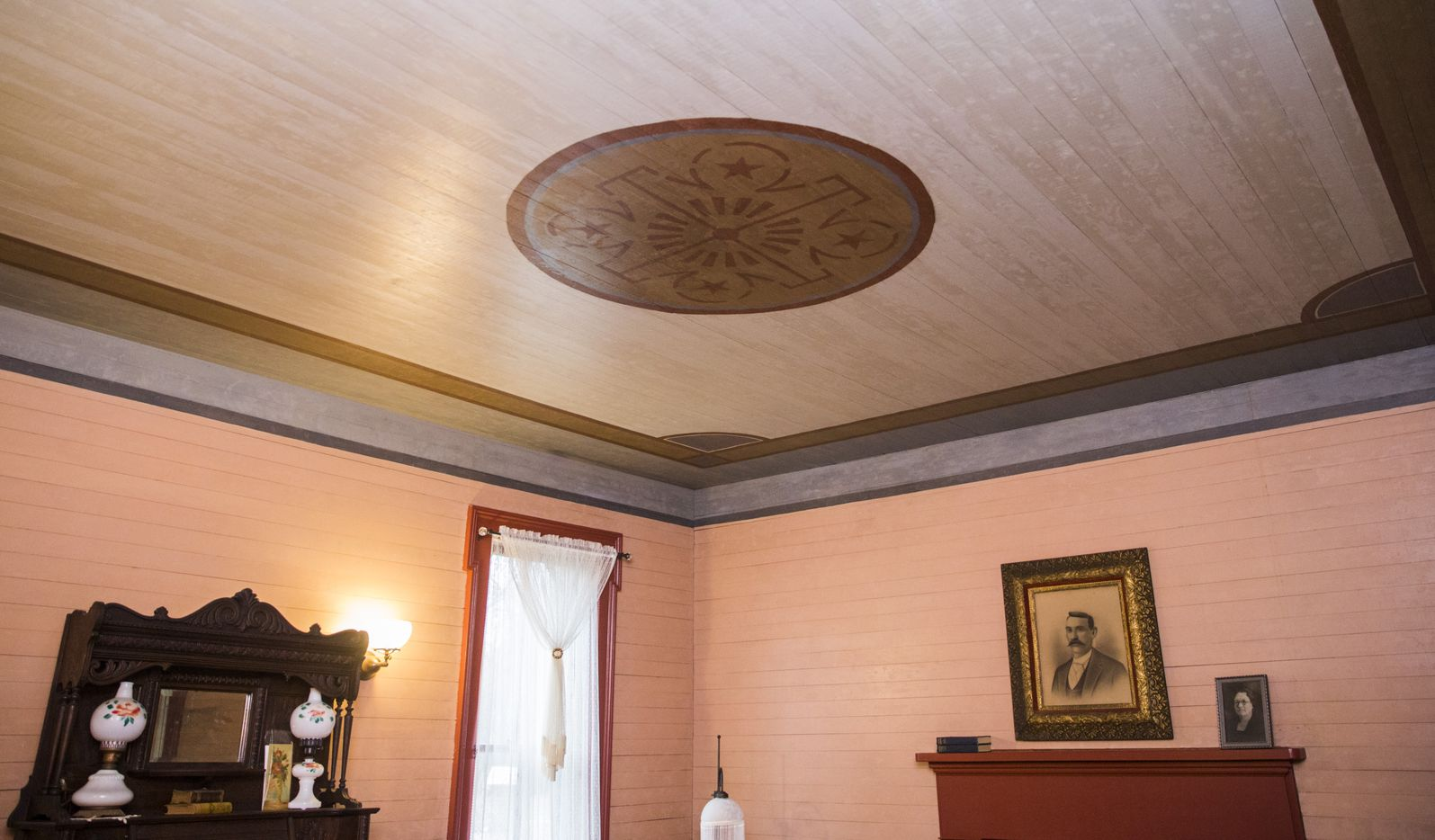 A painted ceiling in the music room inside the Lawrence House was among the discoveries that restorers made when multiple layers of wallpaper were removed.