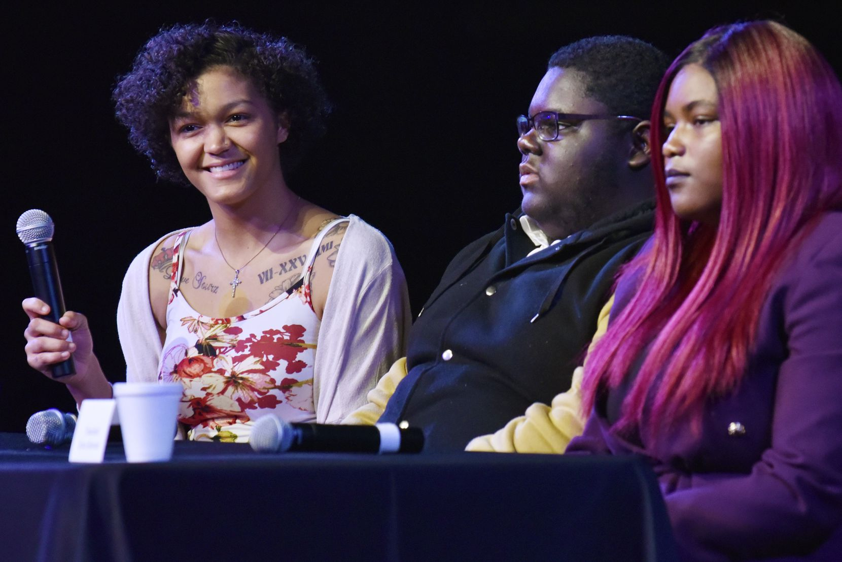 Justice Pearson (left), 18, smiles with tears in her eyes while speaking alongside Joshua Lewis, 14, and Kyra Burton, 19, about important people in their lives who have helped them while experiencing homelessness, at the Youth Homeless Address: Call to Action, hosted by the Metro Dallas Homeless Alliance Youth Committee, at Lovers Lane United Methodist Church in Dallas, Nov. 19, 2019.