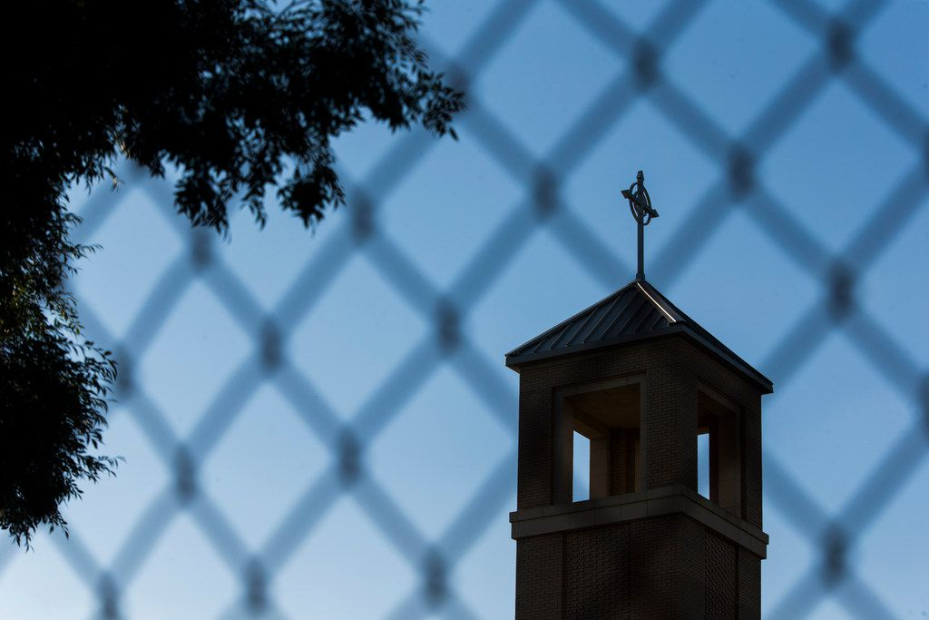 The steeple is seen through a fence outside of St. Cecilia Catholic Church during an evening mass on Wednesday, May 15, 2019 in Dallas. Dallas police raided the Catholic Diocese of Dallas earlier today after an investigation into child sexual abuse allegations against a former priest uncovered claims against others.
