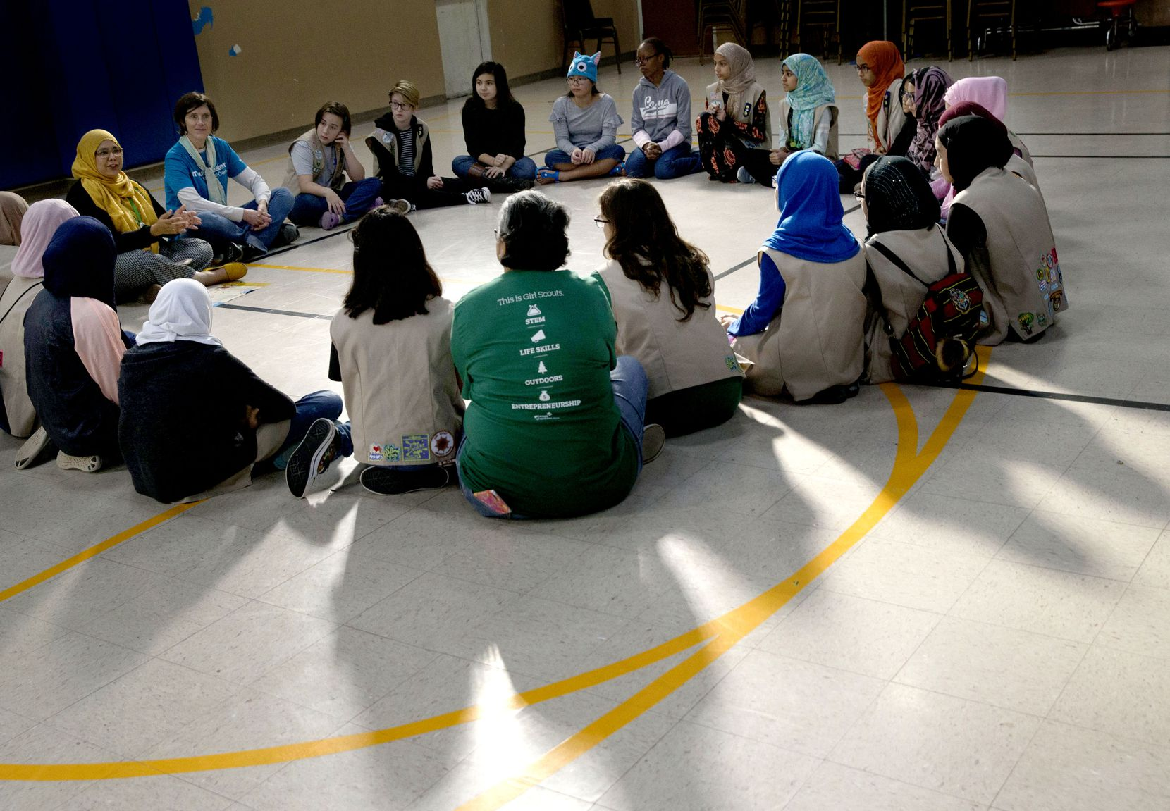 Girl Scouts from Troop 882 and Troop 5309 (both non-Muslim), and Troop 647, a Muslim troop, listen to Troop 647 leader Sharmina Zaidi, far left in yellow, as they begin their combined meeting at the Islamic Association of North Texas mosque in Richardson, Texas on Saturday, November 3, 2018.