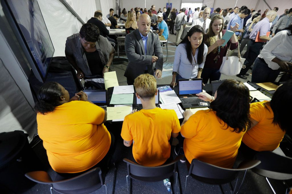 In this Wednesday, Aug. 2, 2017, file photo, job candidatessign in for a job fair at the Amazon fulfillment center in Robbinsville Township, N.J.
