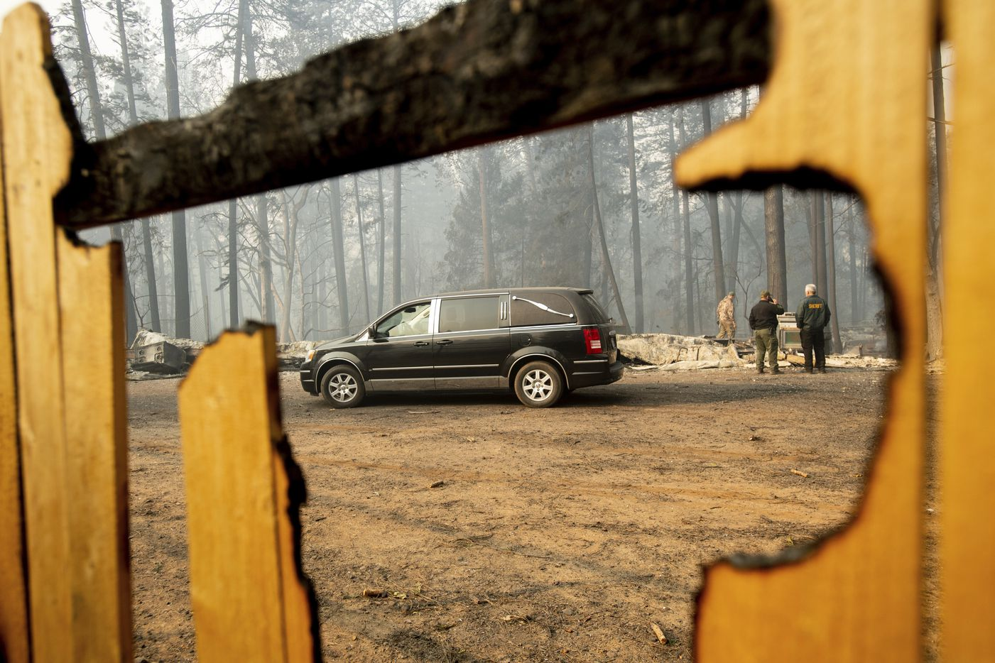 Sheriff's deputies search for human remains at a residence destroyed by the Camp Fire on Nov. 10, 2018, in Paradise, Calif. The hearse carries multiple victims.