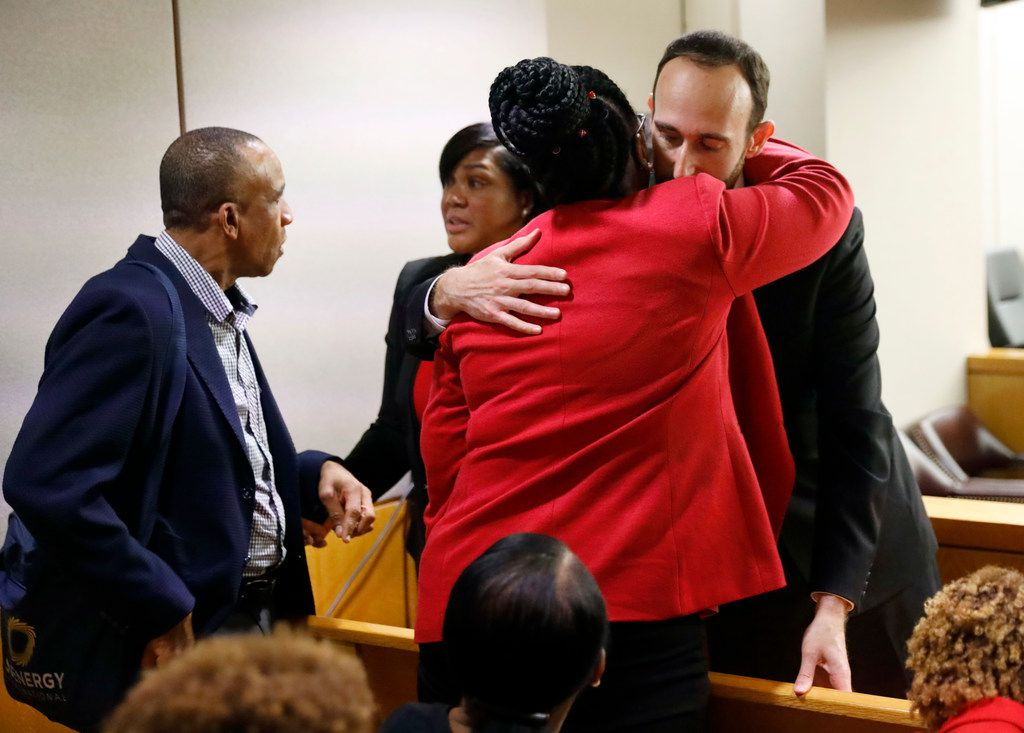 Assistant District Attorney Jason Fine (right) gives Botham Jean's mother, Allison Jean, a hug after closing arguments in the murder trial of fired Dallas police Officer Amber Guyger on Monday, Sept. 30, 2019.