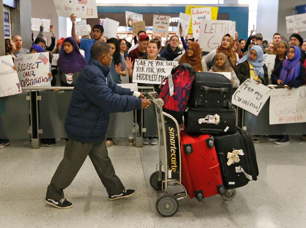Arriving passengers pass through the gauntlet formed by protestors at the international arrivals gate in Terminal D at DFW Airport on Sunday, January 29, 2017. (Louis DeLuca/The Dallas Morning News)