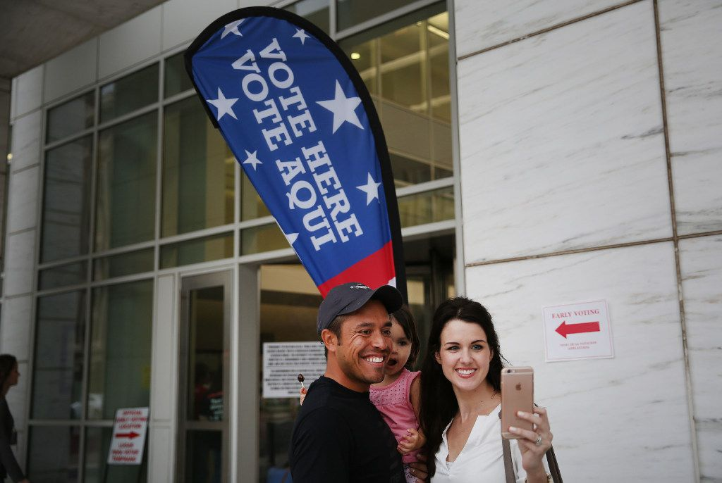 Carlos Aguirre and Melissa Aguirre of Richardson takes a selfie with their daughter, Mia Aguirre, 2, after voting during early voting at the George L. Allen Sr. Courts Building in downtown Dallas.