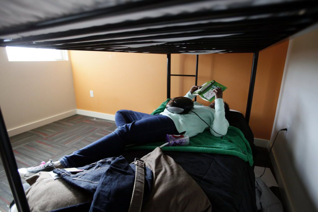A 13-year-old girl relaxes on a bed at Promise House, which is a Dallas nonprofit that helps homeless, runaway and at-risk youth.