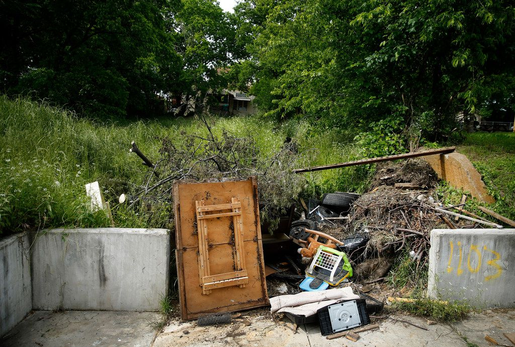 Debris and garbage is piled into a driveway opening leading to a home-less piece of property on Church Street in the Tenth Street Historic District.