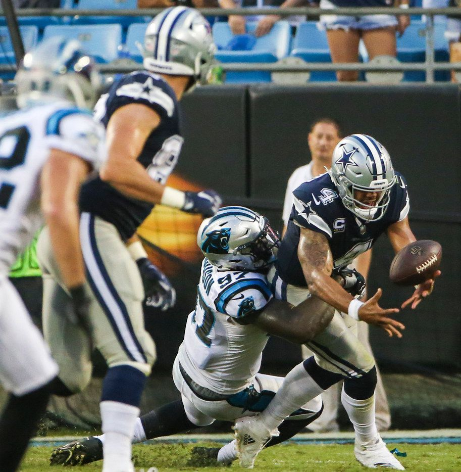 Dallas Cowboys quarterback Dak Prescott (4) fumbles the ball as he is brought down by Carolina Panthers defensive end Mario Addison (97) during the Dallas Cowboys 16-8 loss to the Carolina Panthers on Sunday, Sept. 9, 2018 at Bank of America Stadium in Charlotte, North Carolina. (Ryan Michalesko/The Dallas Morning News)