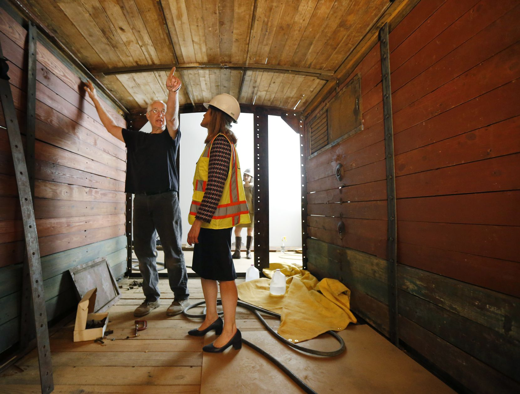 Historic preservationist Ron Siebler shows Mary Pat Higgins, president and CEO of the Dallas Holocaust Museum, the latest progress on the boxcar's installation Friday in the West End.