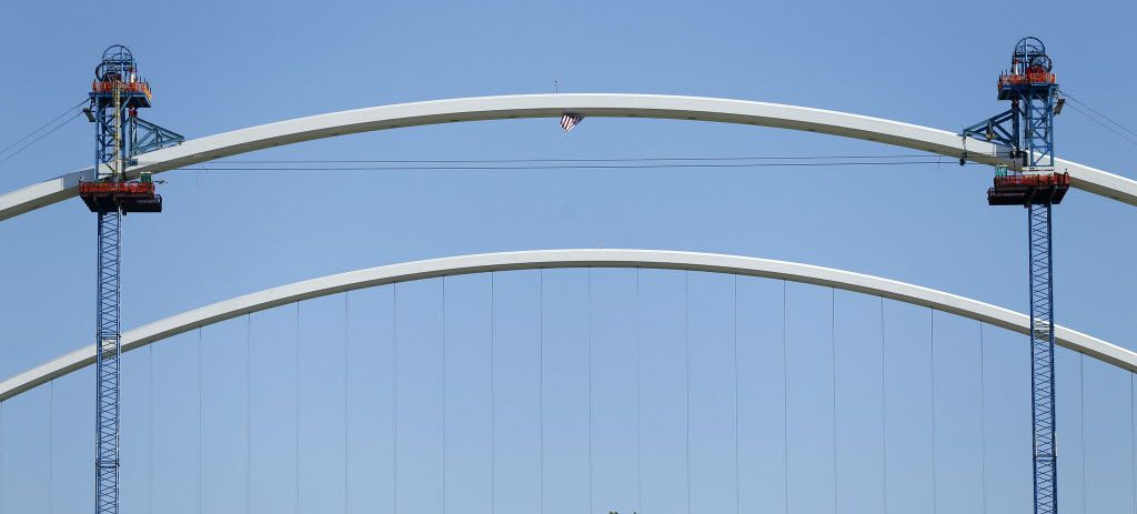 A U.S. flag flies from beneath the final arch segment (top) of the second Margaret McDermott Bridge being built alongside Interstate 30 crossing the Trinity River in Dallas, Friday, July 22, 2016. The arch piece, raised by strand jacks (left and right) attached to the center support towers, completes the arch on the second bridge.  The first arch, which was completed last August, is pictured below. The Santiago Calatrava designed bridge will give pedestrian and bicycle access in and out of downtown Dallas, the floodway and Oak Cliff. (Tom Fox/The Dallas Morning News)