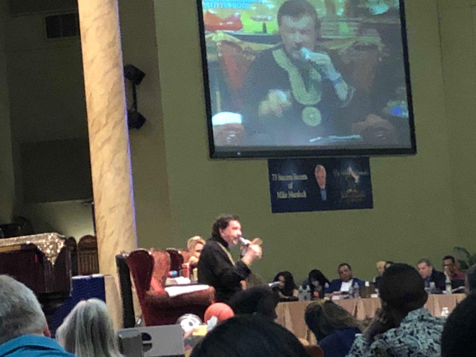 Mike Murdock preaches in front of several hundred people and four TV cameras at his Haltom City complex. He posts his sermons about money on the web and also presents them on religious TV stations across the U.S.