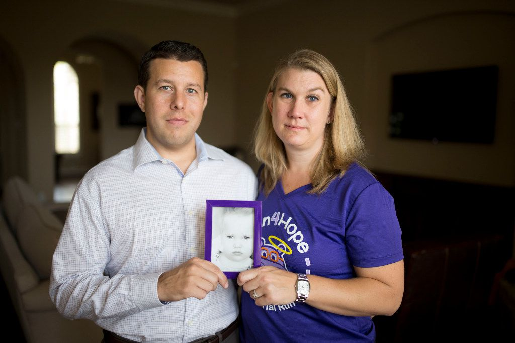 Dustin and Penny Howard pose for a portrait with a photo of their late daughter, Harper, at their home in The Colony. After she died Jan. 8, her parents donated her brain and a deep tissue sample for scientific research. (Ting Shen/Staff Photographer)