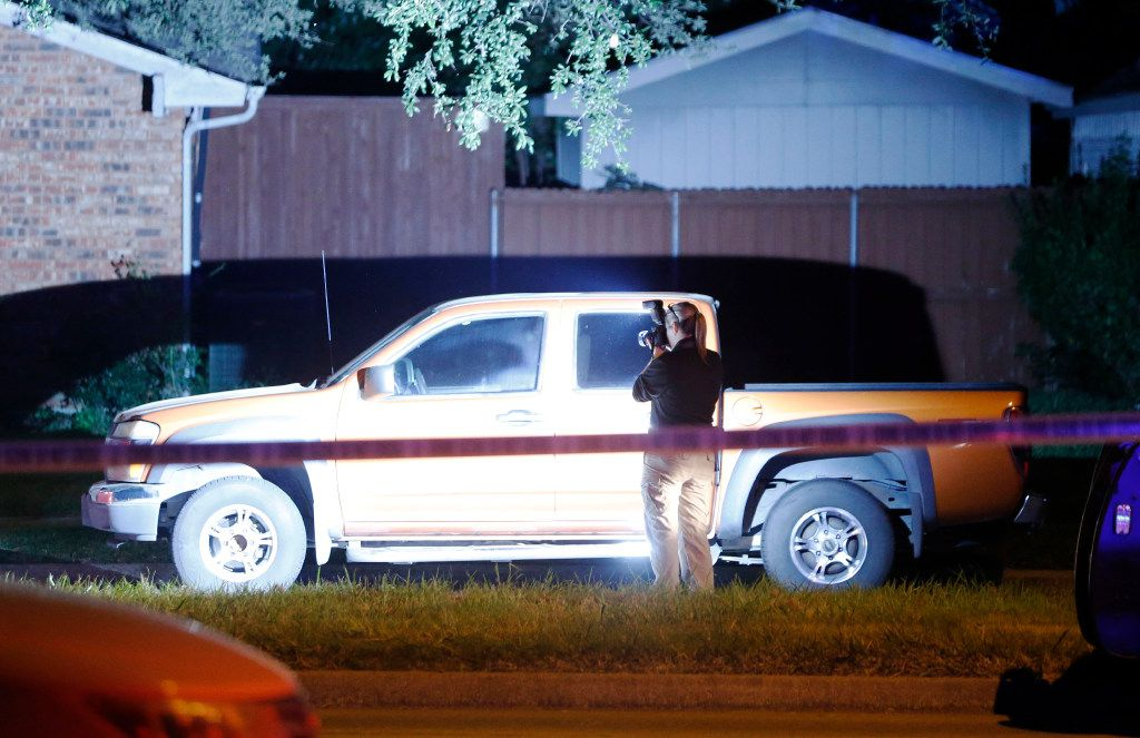 A police investigator takes photos at the scene of the shooting.