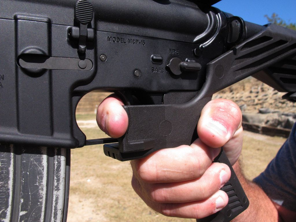 "Shooting instructor Frankie McRae illustrates the grip on an AR-15 rifle fitted with a ""bump stock""  in Bunnlevel, N.C. The stock uses the recoil of the semiautomatic rifle to let the finger ""bump"" the trigger repeatedly, causing it to fire shots in rapid succession."