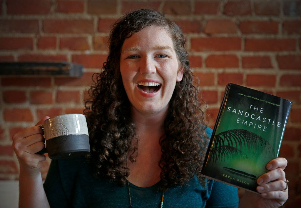 Author Kayla Olson with a coffee mug and her book,  The Sandcastle Empire,  at West Oak Coffee Bar in Denton. (Jae S. Lee/Staff Photographer)