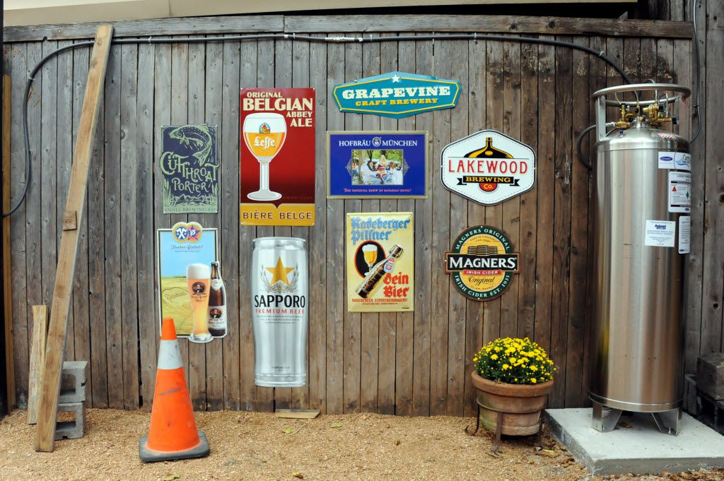 Beer signs decorate the fence at Eight Bells Alehouse in Expo Park Dallas, TX on August 29, 2015.