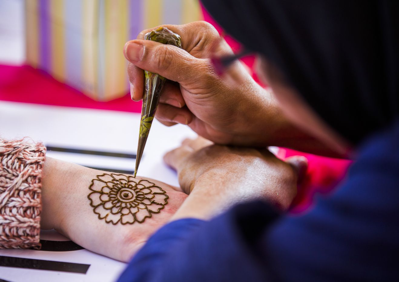 Samober Moosa of the India Association of North Texas applies henna to a woman's hand during the 27th Home Depot Asian Festival on Saturday, May 13, 2017 at Cotton Bowl Plaza in Dallas Fair Park.