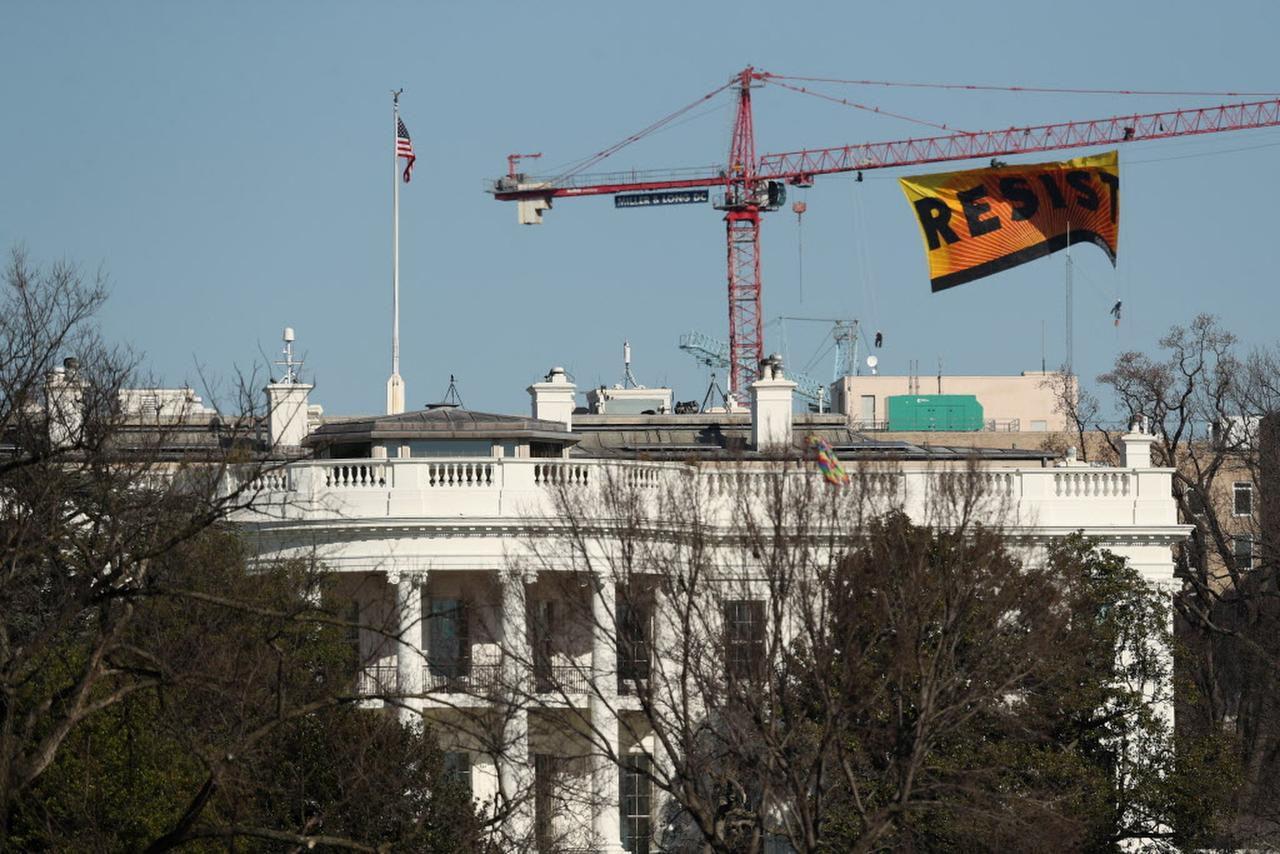 """Unos manifestantes de Greenpeace despliegan un baner que dice """"resiste"""" frente a la Casa Blanca, el miércoles, 25 de enero del 2017. (AP/ANDREW HARNIK)"""