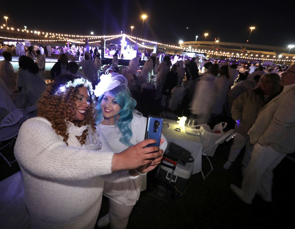Shawnte Johnson, left, and Gigi Arizmendi take a selfie during Diner En Blanc. The backdrop of the city skyline made the event great for photos.