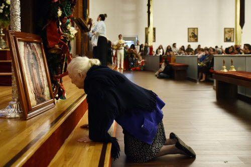 Una anciana se arrodilla ante una imagen de la Virgen de Guadalupe en la iglesia San Juan Diego.