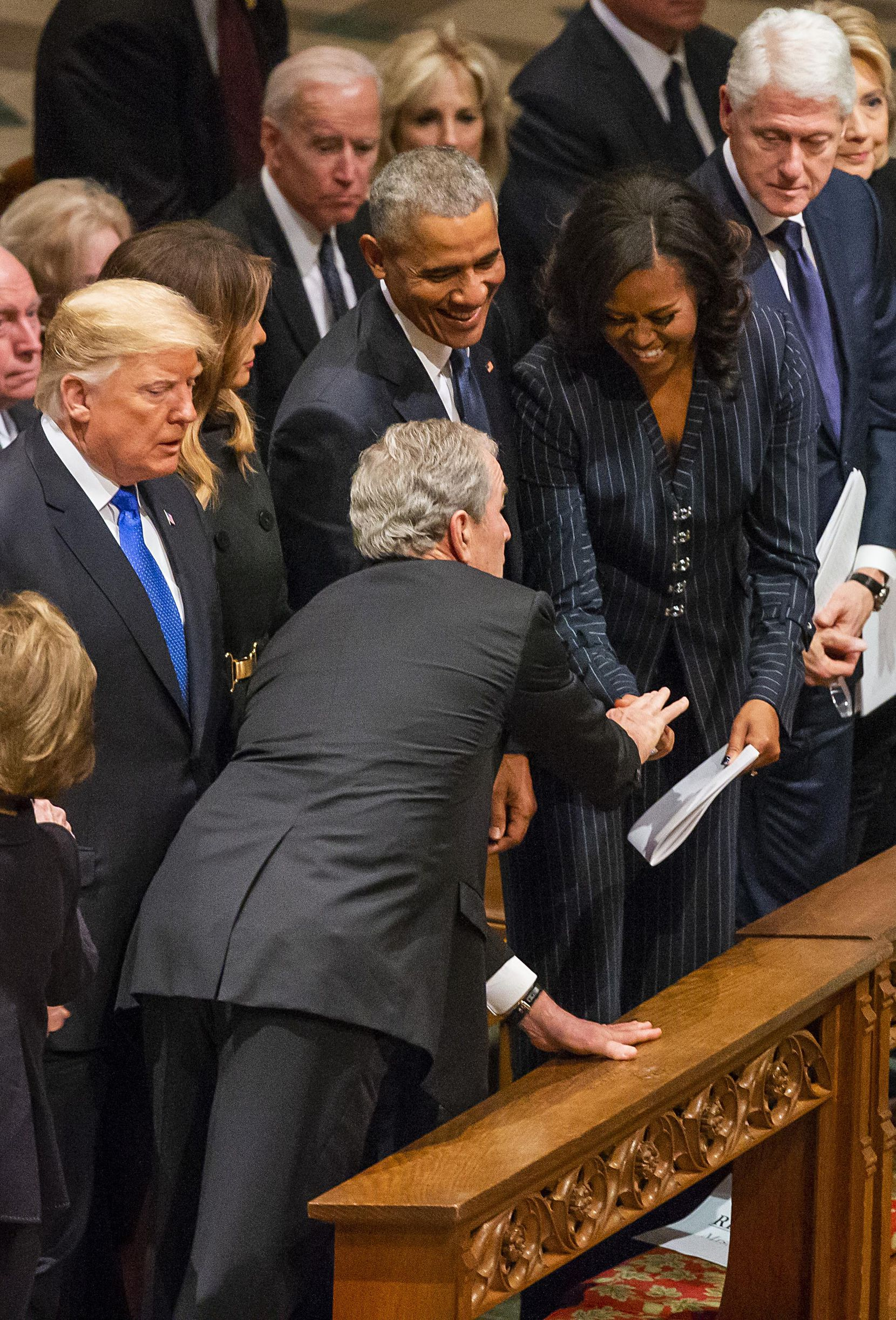 Former President George W. Bush, hands something to a laughing Michelle Obama as (from left) President Donald Trump, first lady Melania Trump, former President Barack Obama, former President Bill Clinton and former Secretary of State Hillary Clinton, look on before Bush took his seat for the State Funeral for George H.W. Bush, the 41st President of the United States, at the Washington National Cathedral on Wednesday, Dec. 5, 2018, in Washington.
