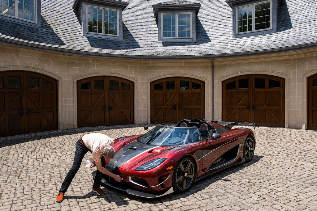 Ted Skokos wipes down a Koenigsegg Agera RS on display in the driveway of his carriage house.