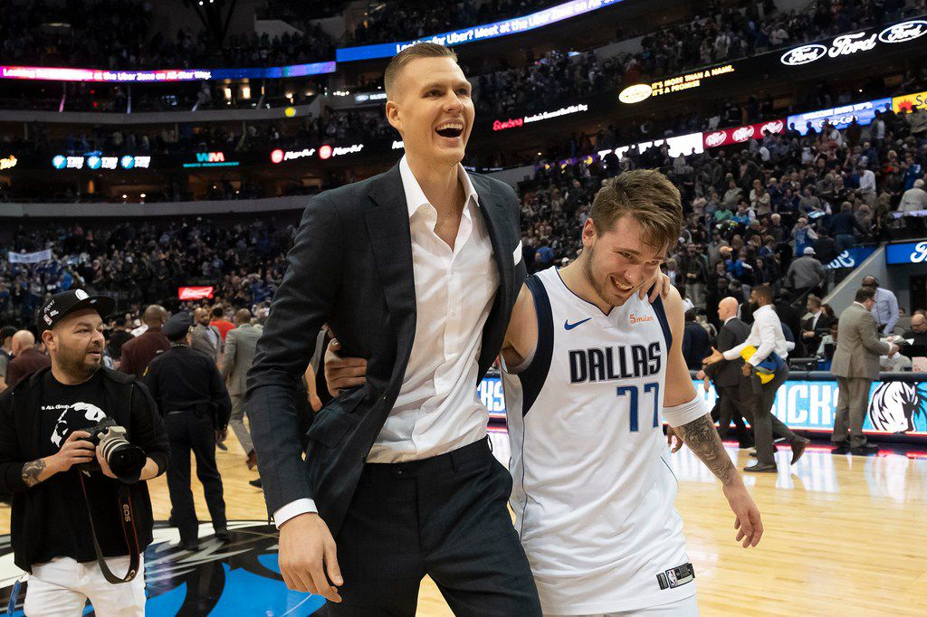 Dallas Mavericks forward Luka Doncic (77) hugs forward Kristaps Porzingis as they walk off the floor following a victory over the Portland Trail Blazers an NBA basketball game at American Airlines Center on Sunday, Feb. 10, 2019, in Dallas.