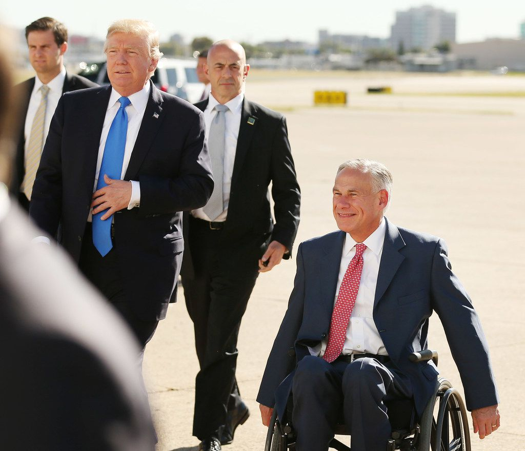 President Donald Trump and Texas governor Greg Abbott greet supporters after Trump arrived at Love Field in Dallas Wednesday October 25, 2017. President Trump will participate in a hurricane recovery briefing, a Republican National Committee roundtable and give remarks at a reception. (Andy Jacobsohn/The Dallas Morning News)