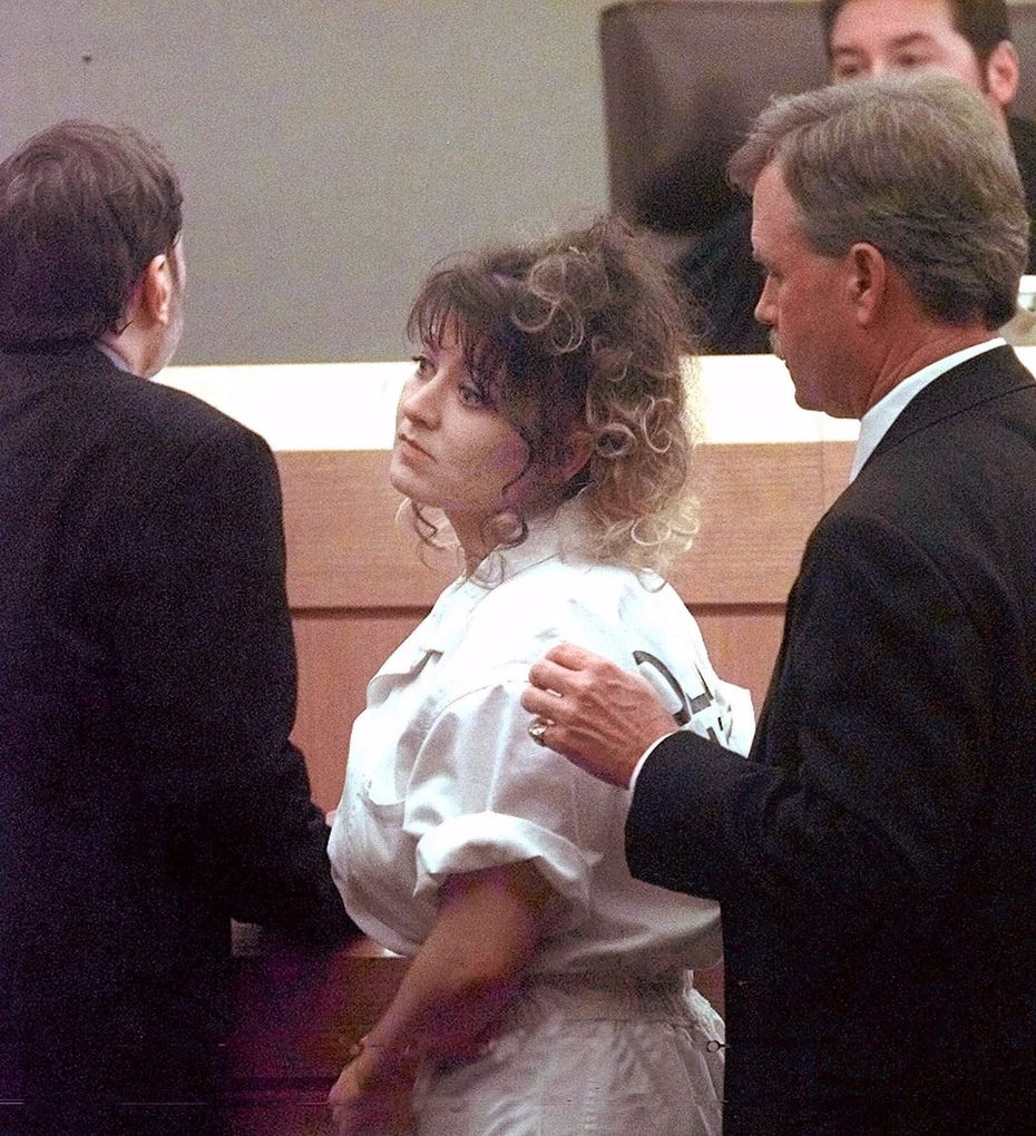 Darlie Routier, on death row for the murder of her 5-year-old son, turns at the close of her court hearing in Dallas on Oct. 30, 1998. Flanking Routier are her attorneys Stephen Cooper (left) and Steve Losch. At rear is Judge Robert Francis.