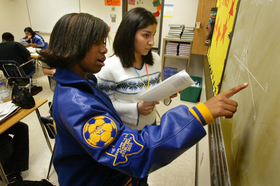 In 2004, Lakeview Centennial High School junior Adrienne Reese, front, helps fellow AVID (Advancement Via Individual Determination) classmate Sandra Colunga, back, with a SAT practice test problem during class.