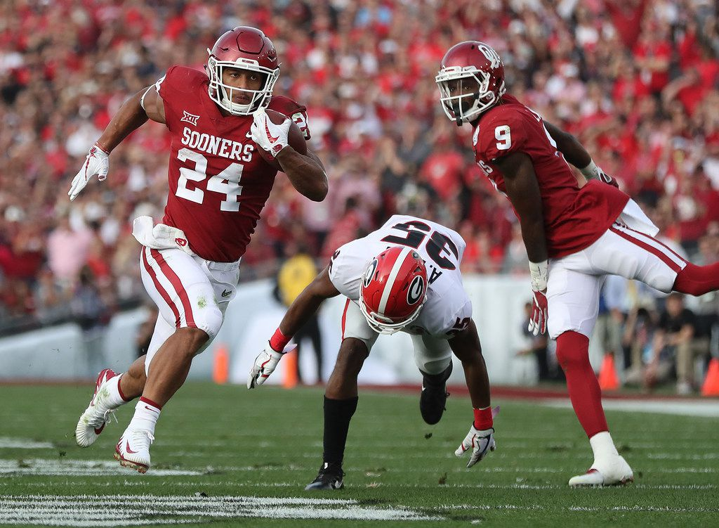 Oklahoma running back Rodney Anderson breaks away from Georgia defensive back Aaron Davis for a touchdown to take a 21-7 lead during the second quarter in the College Football Playoff Semifinal at the Rose Bowl Game on Monday, Jan. 1, 2018, in Pasadena, Calif. (Curtis Compton/Atlanta Journal-Constitution/TNS)