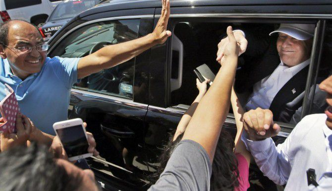 Simpatizantes extiende la mano para saludar al aspirante republicano Donald Trump, en Laredo, Texas. (AP/LM OTERO)